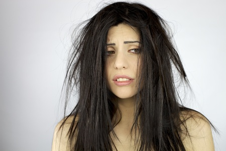 bad hair day: Sad and depressed woman with terrible mess on her hair Stock Photo
