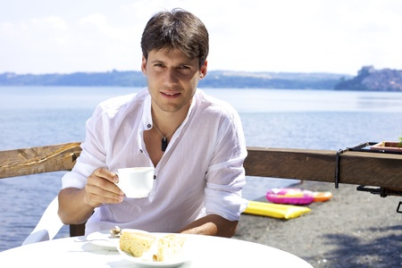 Good looking young man drinking coffee relaxed in front of lake smiling