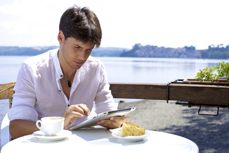 Young man in italy reading tablet during breakfast in front of beautiful lakez