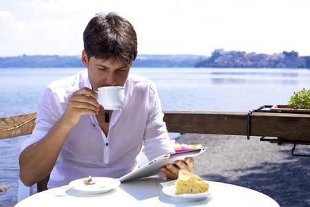 drinking tea: Good looking man drinking cappuccino in front of lake working with electronic tablet