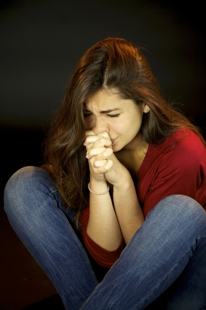 Scared young woman crying and praying Stock Photo - 15761460