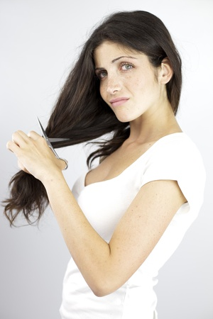 Young woman sad of cutting her hair with scissors photo