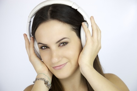 Young woman listening music with white headphones photo