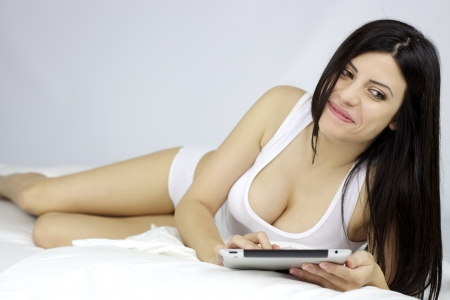 prosperous: Gorgeous prosperous female model happy laying in bed Stock Photo