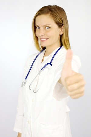 Beautiful blond female doctor showing thumb up smiling happy Stock Photo - 16640298