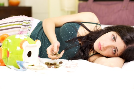 Woman at home laying in bed desperate not having a job left with few money photo
