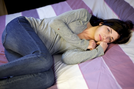 Depressed young woman in bed after domestic violence at home photo