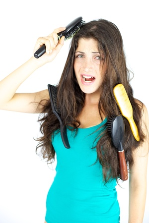 Woman stuck with brushes in her hair screaming loud, tangled hair photo