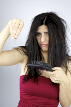 alopecia: Unhappy woman holding lost hair in hand Stock Photo