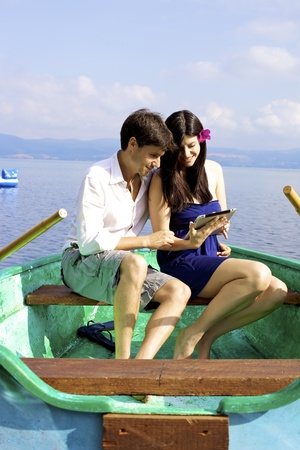 Happy couple sitting on green boat in vacation reading electronic tablet ipad photo