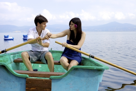 Couple arguing on boat while rowing photo