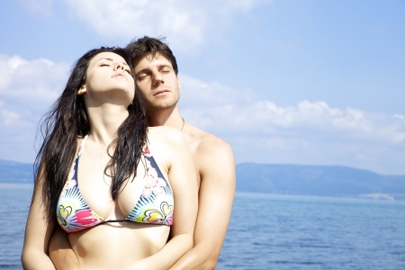 Happy couple in love in swimwear getting tanned in Italy photo
