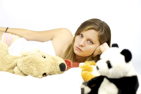 Depressed woman in bed with stuffed pet and toys with her