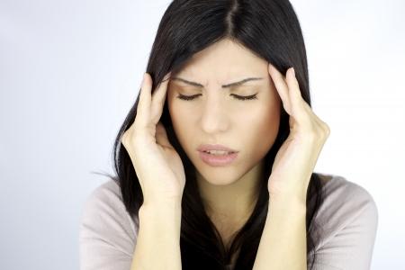 dolor de cabeza: Mujer que toca la cabeza tratando de calmar el dolor Foto de archivo