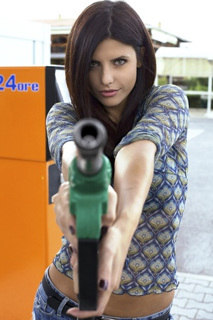 Perfect beauty at gas station holding as gun gas pump