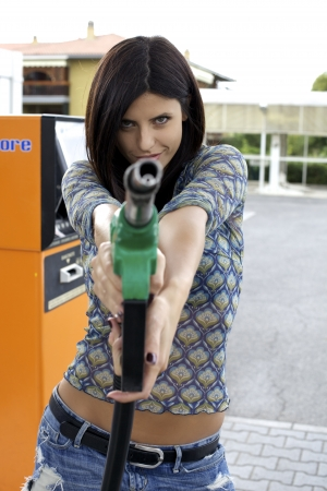 gasoline: Strong woman holding gas pump