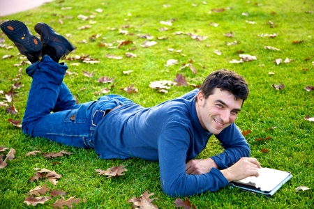 Good looking male model laying in park with tablet smiling photo