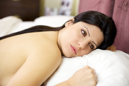 Sadness and loneliness captured young woman in bed feeling lonely photo