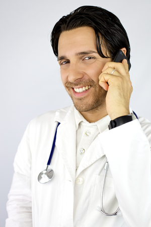 Happy young cool doctor smiling while talking on the phone photo