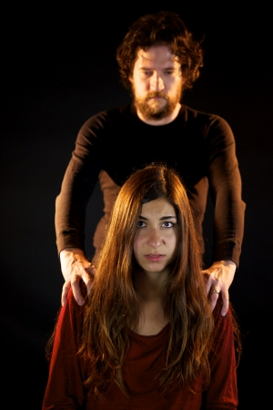 Angry man scaring young woman photo