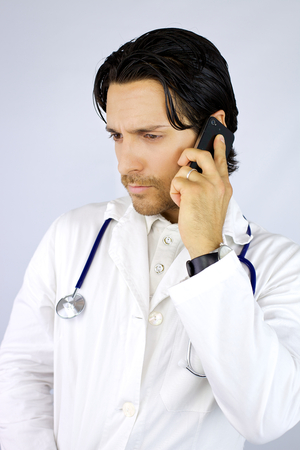 important phone call: Doctor listening to important phone call Stock Photo