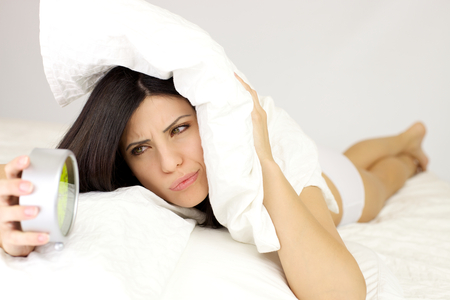 Woman holding alarm clock unhappy photo