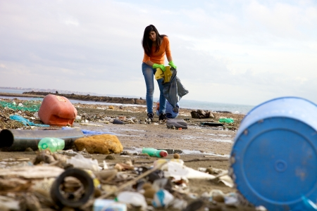 Ecological disaster on the sea woman cleaning dirt
