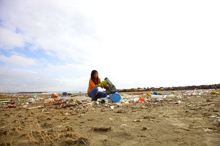 Young woman trying to clean ecological disaster