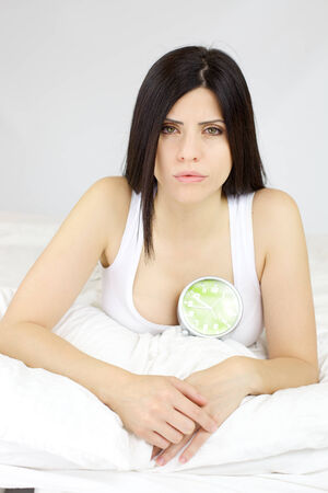 Beautiful woman with heart problem with alarm clock showing end of time photo