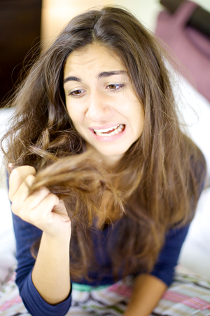 Woman holding destroyed hair with split ends