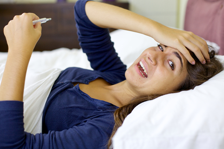 Sick woman in bed measuring with thermometer flu photo