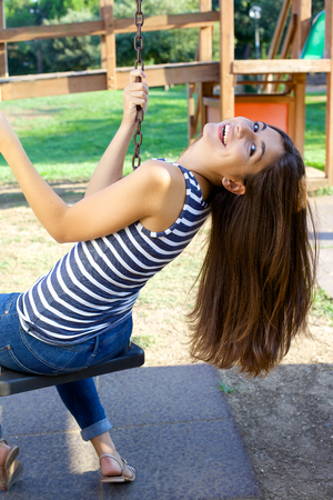 Young woman having fun on swing in park in summer smiling photo