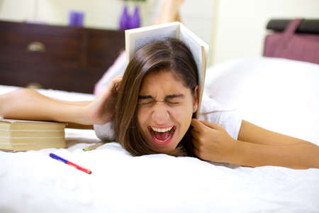 Girl in bed screaming tired of studying photo