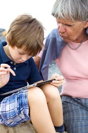 Happy kid playing with tablet and grandmother photo