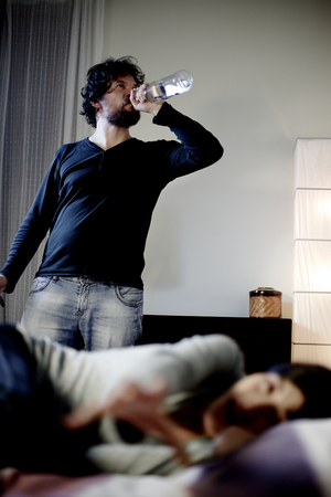 Man drinking alcohol while wife is screaming in bed