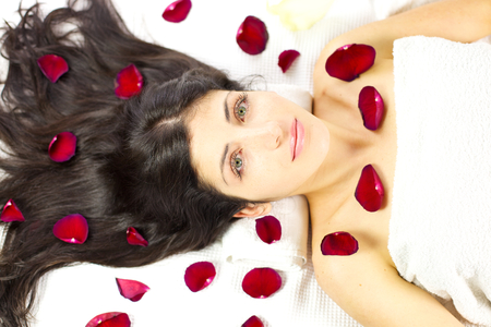 Gorgeous woman with blue green eyes laying in spa with rose photo