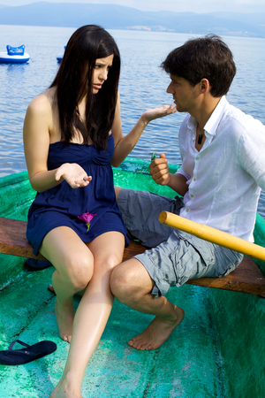 Young couple fighting on boat on lake in Italy photo