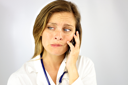 Woman doctor feeling sad on the phone because of bad news photo