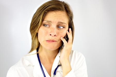 Woman doctor feeling sad on the phone because of bad news photo