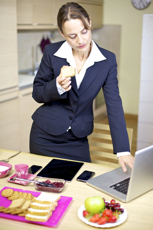 Beautiful business woman dressed for work emailing during breakfast photo