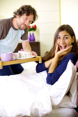 spoiling: Happy couple in vacation with continental breakfast in hotel room