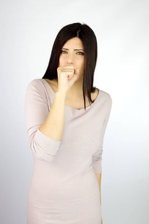 Beautiful ill woman coughing strong with hand in front of mouth photo