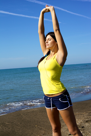 Gorgeous female model doing sport in front of the ocean while listening earphone radio photo
