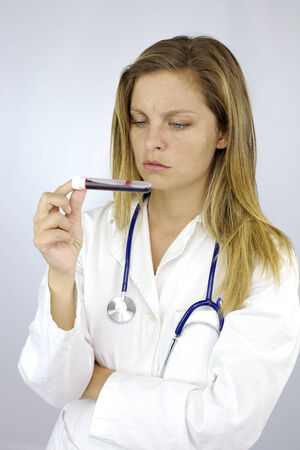 Young student doctor observing test of blood photo