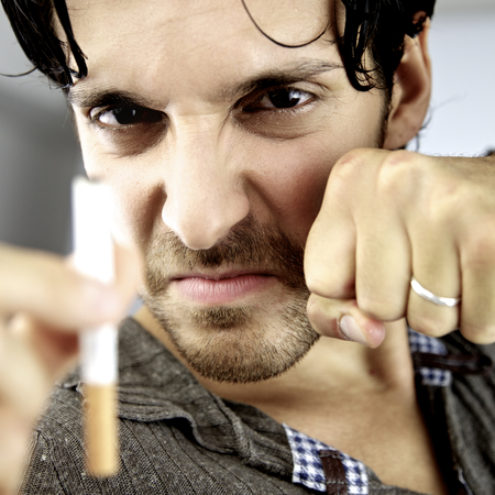 Angry man fighting with cigarette willing to stop smoking