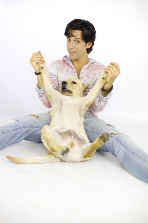Happy man having fun with his labrador in studio photo