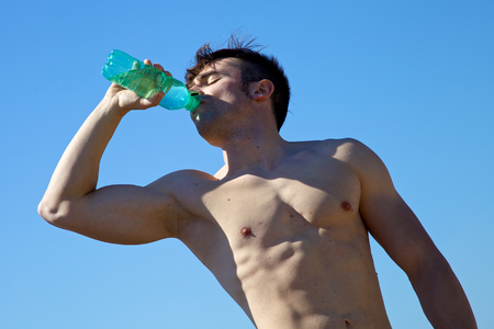 Cool muscular man drinking water in front of the sky photo