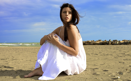Gorgeous woman sitting on beach with white dress photo