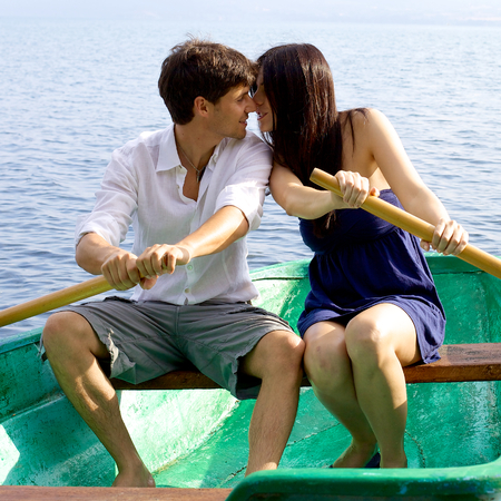 Happy couple kissing in vacation rowing boat photo