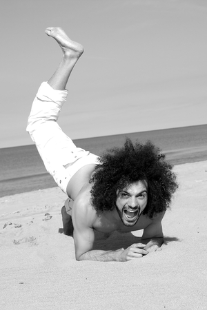 Black and white portrait of happy man playing on the beach in summer photo